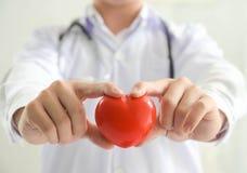 Doutor novo que guarda uns cuidados médicos vermelhos do coração e um conceito médico Imagens de Stock