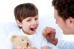 Doutor novo que toma a temperatura do rapaz pequeno Foto de Stock Royalty Free