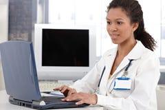 Doutor novo que trabalha no sorriso do computador portátil Fotografia de Stock