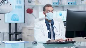 Doutor novo que veste uma máscara que datilografa no computador filme