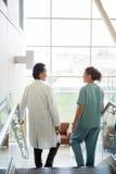 Doutor And Nurse Conversing ao andar para baixo foto de stock royalty free