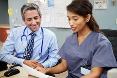 Doutor With Nurse Working na estação das enfermeiras Foto de Stock Royalty Free