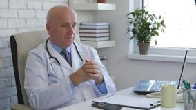 Doutor Office Job Sitting na mesa e no pensamento foto de stock