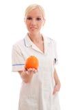 Doutor ou enfermeira com laranja Fotografia de Stock