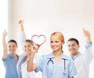 Doutor ou enfermeira de sorriso que tiram o coração vermelho Fotografia de Stock Royalty Free