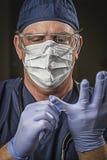Doutor ou enfermeira de vista determinada com desgaste protetor e Stet Fotografia de Stock Royalty Free
