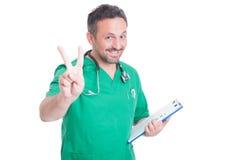 Doutor ou médico bem sucedido que mostram o gesto da paz Fotografia de Stock