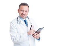 Doutor ou médico de sorriso que usa o cartão de crédito e a tabuleta sem fio Imagens de Stock