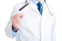 Doutor ou médico anônimo que mostram o crédito e o cartão de crédito Foto de Stock Royalty Free