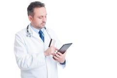Doutor ou médico que usa o cartão de crédito e a tabuleta sem fio Imagem de Stock