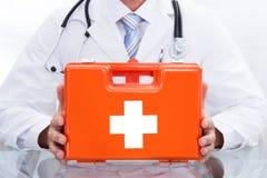 Doutor ou paramédico de sorriso com um kit de primeiros socorros Fotografia de Stock Royalty Free