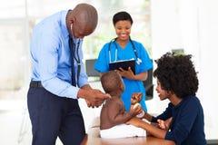 Doutor pediatra que examina foto de stock
