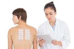 Doutor pelo paciente que guarda a tabuleta digital Fotografia de Stock