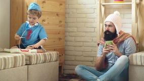Doutor pequeno e seu paciente O pai e o filho têm o divertimento que joga o tempo Conceito da medicina, dos cuidados médicos e da