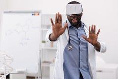 Doutor profissional considerável que pressiona suas mãos à tela virtual Imagens de Stock