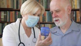 Doutor profissional fêmea no trabalho Médico superior que consulta o paciente doente em casa sobre comprimidos novos video estoque