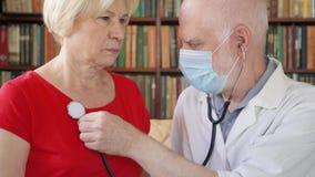 Doutor profissional masculino no trabalho Equipe o médico que usa o estetoscópio para os pulmões pacientes de escuta do ` s filme