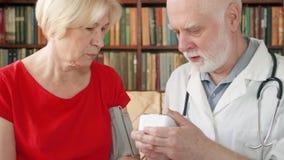 Doutor profissional masculino no trabalho Medida superior da pressão do médico ao paciente pelo tonometer em casa vídeos de arquivo