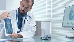 Doutor profissional que guarda uma tabuleta do PC nas mãos e que explica algo em uma varredura de X Ray video estoque