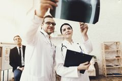 Doutor qualificado com raio X de exame do estetoscópio e da enfermeira do homem de negócios na clínica foto de stock