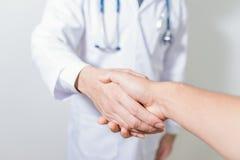 Doutor que agita um patient& x27; mãos de s no fundo branco Foto de Stock Royalty Free