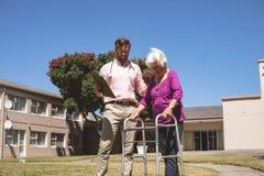 Doutor que ajuda a mulher superior com seu caminhante no lar de idosos exterior fotografia de stock royalty free