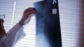 Doutor que analisa o raio X filme