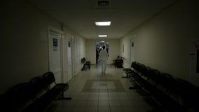 Doutor que anda no corredor do hospital video estoque