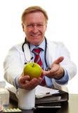 Doutor que aponta a uma maçã Foto de Stock