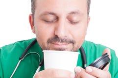 Doutor que aprecia o cheiro ou o café fresco Fotos de Stock Royalty Free