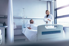 Doutor que atende ao paciente doente na cama de hospital fotos de stock