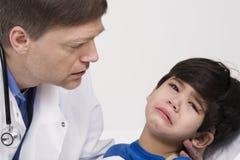 Doutor que consola um rapaz pequeno scared foto de stock royalty free