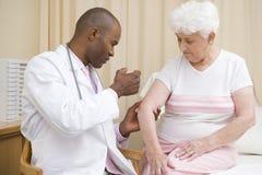 Doutor que dá a agulha à mulher Imagens de Stock