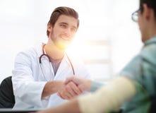 Doutor que dá boas-vindas a um paciente em seu estúdio imagem de stock
