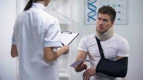 Doutor que dá a conta ao paciente no estilingue do braço e no colar da espuma, tratamento caro vídeos de arquivo