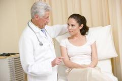 Doutor que dá o controle da mulher no quarto do exame Foto de Stock Royalty Free