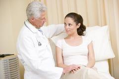 Doutor que dá o controle da mulher no quarto do exame Imagem de Stock
