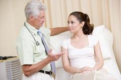 Doutor que dá o controle da mulher no quarto do exame Foto de Stock