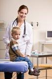 Doutor que dá o controle do menino no escritório do doutor Foto de Stock