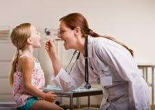 Doutor que dá o controle da menina no escritório do doutor Fotografia de Stock Royalty Free