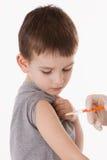 Doutor que dá uma injeção da criança no braço Fotografia de Stock