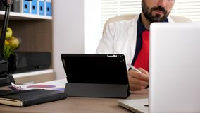 Doutor que datilografa no PC digital da tabuleta video estoque