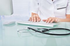 Doutor que datilografa no teclado de computador na clínica Imagens de Stock Royalty Free