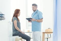 Doutor que diagnostica um paciente fêmea imagem de stock