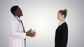 Doutor que diz a boa notícia e as folhas pacientes no fundo do inclinação foto de stock