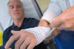 Doutor que enfaixa a mão paciente no escritório médico fotografia de stock royalty free