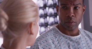 Doutor que entrega más notícias ao paciente preto imagens de stock