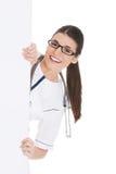 Doutor que esconde atrás de um quadro de avisos Imagens de Stock
