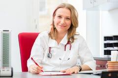 Doutor que escreve a prescrição médica na cirurgia Imagem de Stock Royalty Free