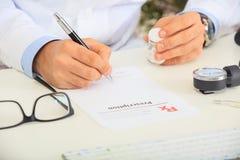 Doutor que escreve um perscription Imagens de Stock